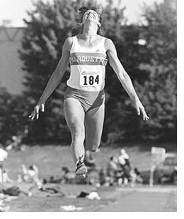 Woman jumps in track and field uniform